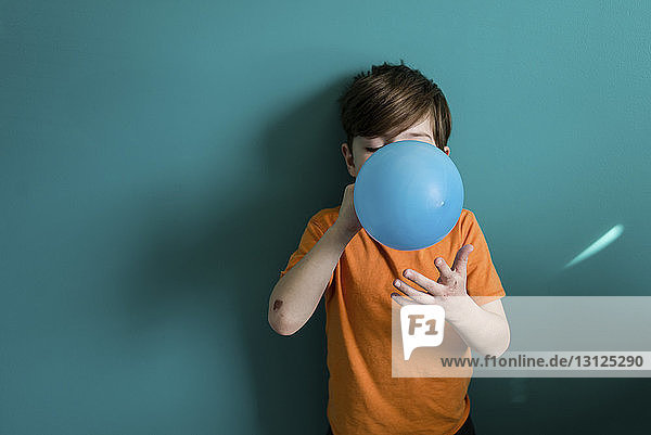Boy blowing balloon while standing against blue wall at home