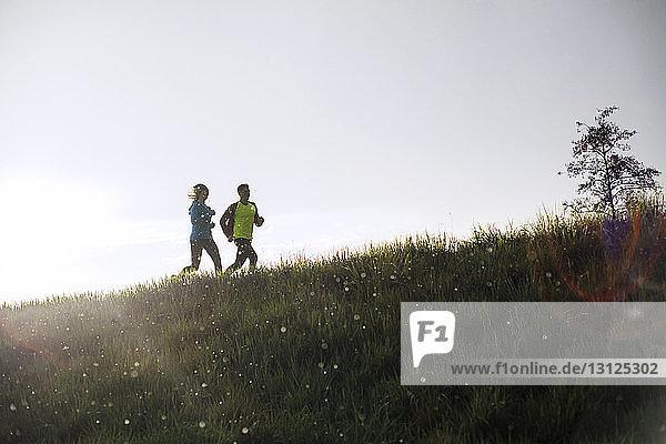 Männliche und weibliche Athleten laufen bei Sonnenuntergang auf Grasfeld