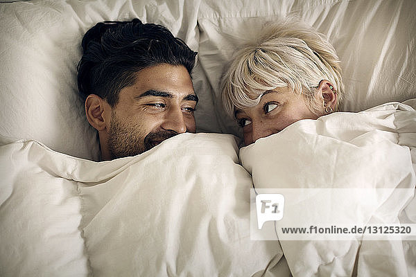 Overhead view of happy couple looking at each other in bed