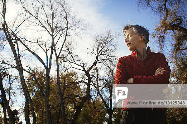 Low angle view of thoughtful woman standing against sky