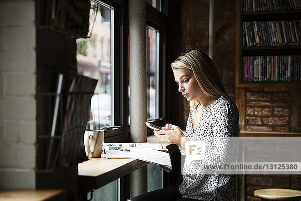 Young woman using phone while reading newspaper at table in cafe