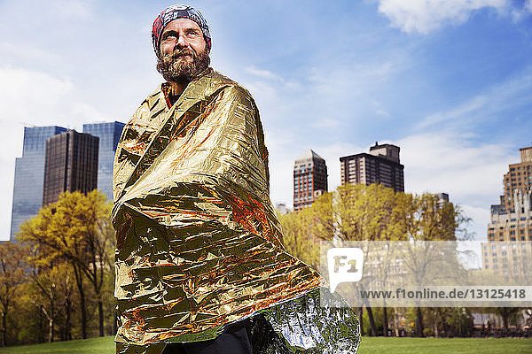 Smiling thoughtful man wrapped in golden sheet standing against city