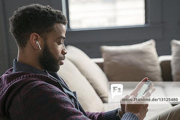 Geschäftsmann benutzt Smartphone  während er im Büro auf dem Sofa sitzt