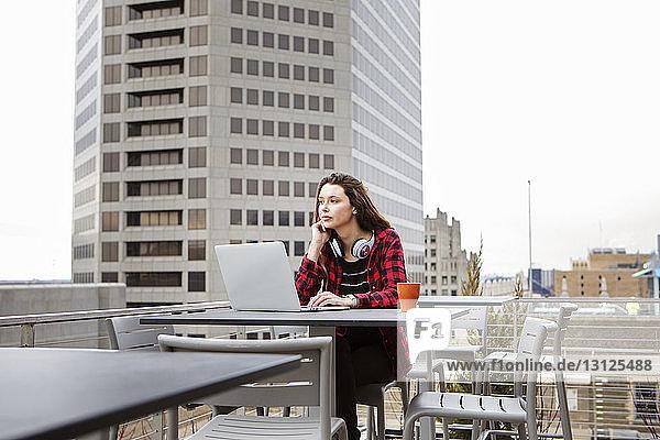 Nachdenkliche junge Frau mit Laptop-Computer sitzt auf einem Stuhl im Terrassencafé