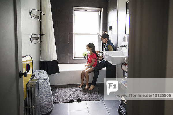 Mother tying hair of daughter while sitting in bathroom
