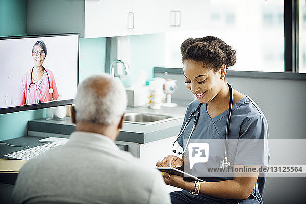 Happy female doctor using tablet computer while sitting with patient in clinic