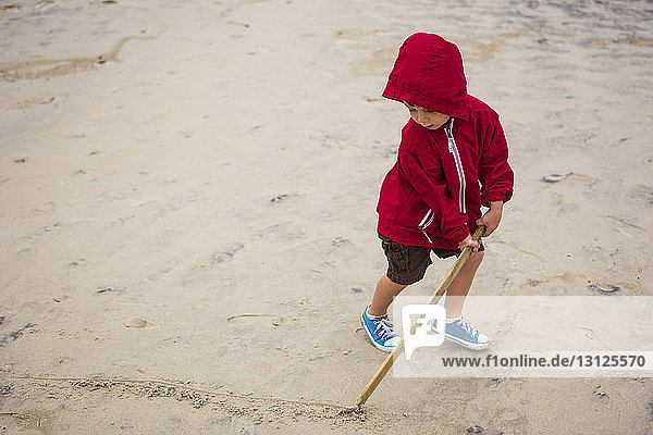 Hochwinkelansicht eines Jungen  der mit einem Stock eine Linie auf Sand zieht