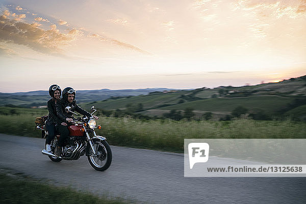 Young couple riding on motorcycle at country road during sunset