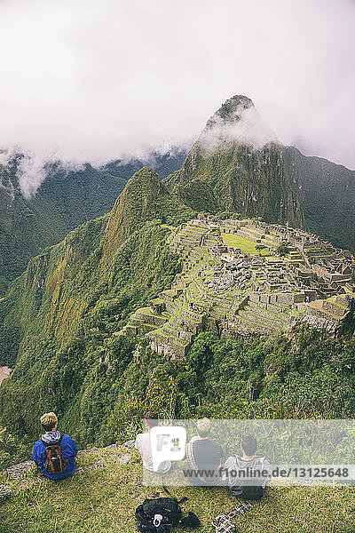 Rückansicht der auf dem Berg sitzenden Freunde gegen Machu Picchu
