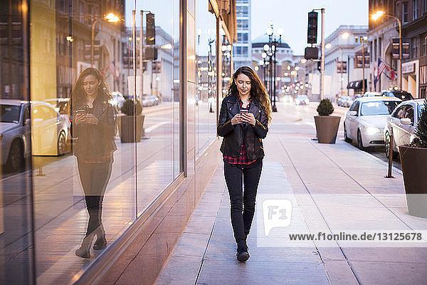 Junge Frau benutzt Smartphone  während sie auf einem Fußweg an Gebäuden vorbei geht