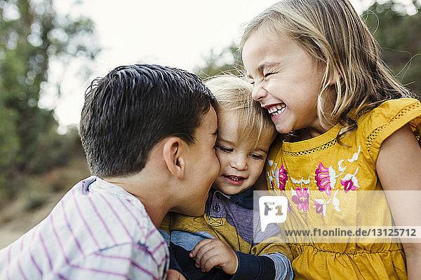 Close-up of cheerful siblings at field