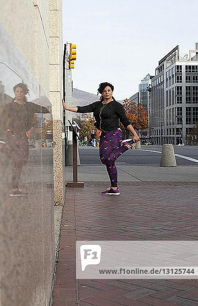 Frau hört Musik  während sie auf dem Bürgersteig gegen den Himmel in der Stadt trainiert