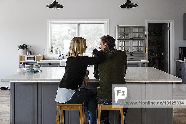 Rückansicht eines auf Hockern sitzenden Paares in der heimischen Küche