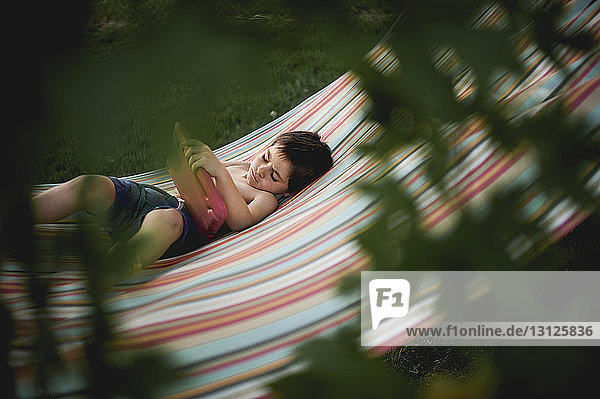 High angle view of boy looking at slate while lying on hammock at backyard seen through branches