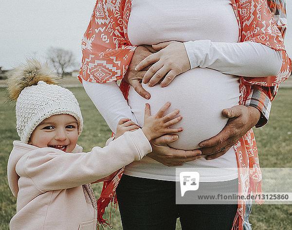 Porträt einer fröhlichen Tochter  die den Bauch der schwangeren Mutter berührt  mit dem Vater auf dem Feld