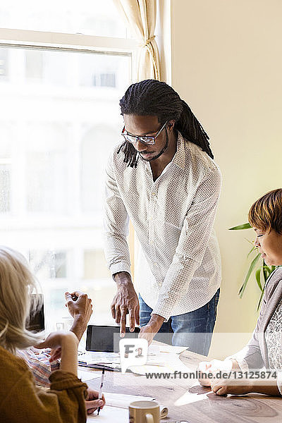 Businessman showing phablet to colleagues in office