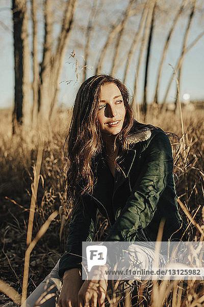 Lächelnde junge Frau schaut weg  während sie auf dem Feld sitzt