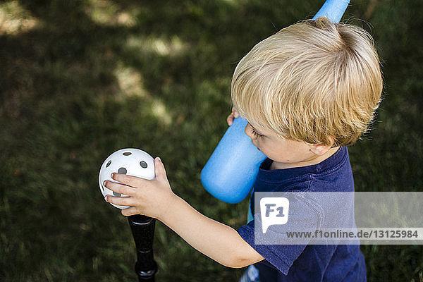 Schrägaufnahme eines T-Ball spielenden Jungen im Hinterhof