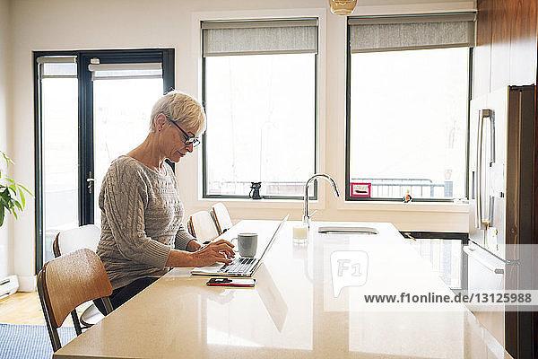 Ältere Frau benutzt Laptop-Computer am Küchentisch zu Hause