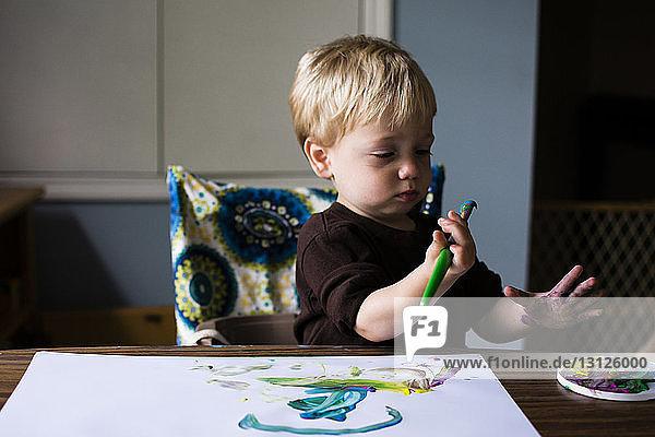 Süßer Junge malt auf Papier  während er zu Hause sitzt