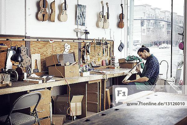 Geigenbauer bei der Arbeit in der Werkstatt