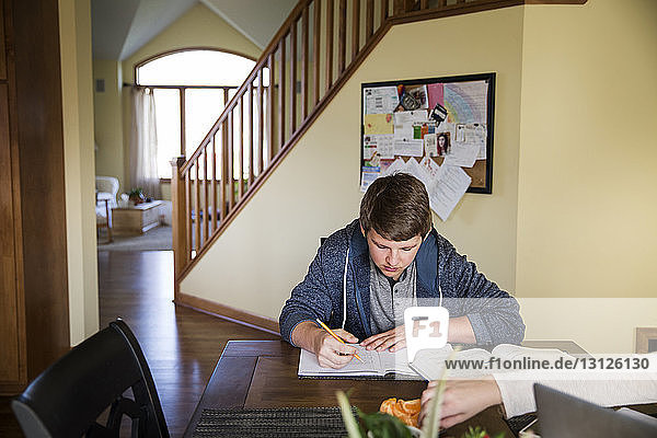 Young man studying on table at home