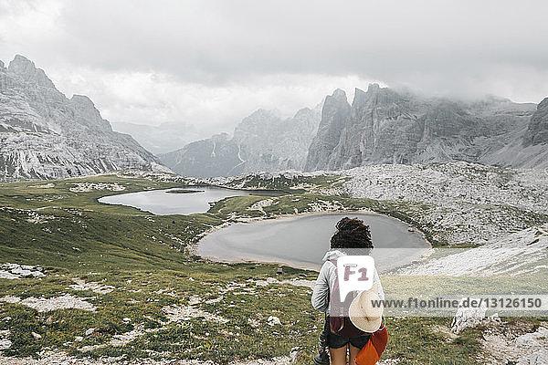 Wanderin mit Rucksack schaut auf die Aussicht  während sie an den Bergen steht