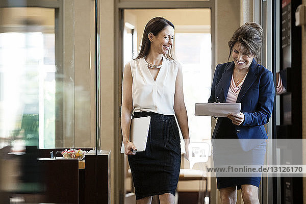 Businesswomen with laptop and notepad walking in office