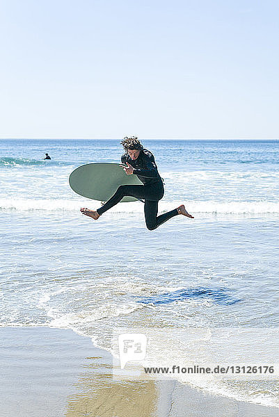 Man with surfboard jumping in sea against clear sky