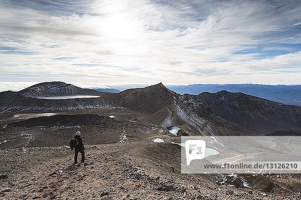 Mann wandert am Mt. Ngauruhoe bei bewölktem Himmel am sonnigen Tag
