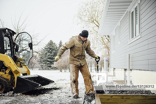 Mann hält im Winter im Hinterhof arbeitende Schaufel gegen den Himmel