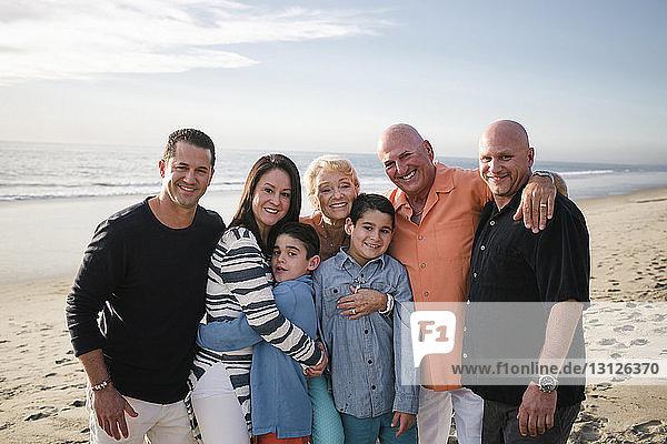 Porträt einer glücklichen Familie  die am Strand gegen den Himmel steht