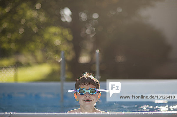 Portrait of happy boy wearing swimming goggles in pool