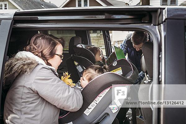 Eltern  die Mädchen auf Autositzen einstellen