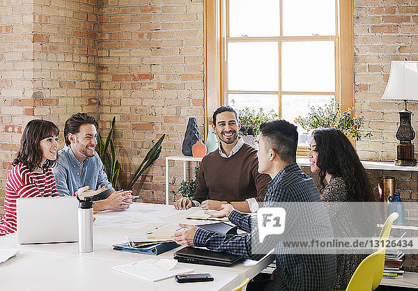 Happy business people sitting at desk during meeting in office