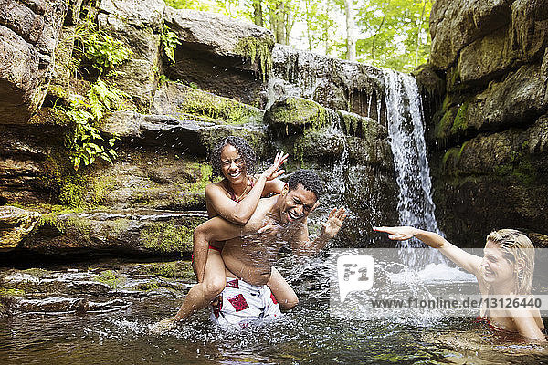 Cheerful friends laughing and splashing in river by waterfall