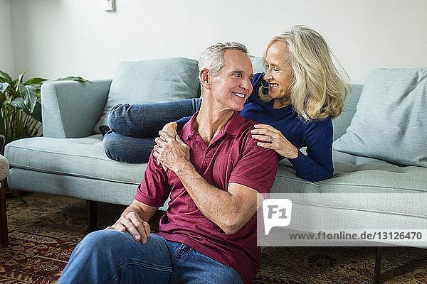 Glückliches Paar unterhält sich  während es sich zu Hause im Wohnzimmer ausruht