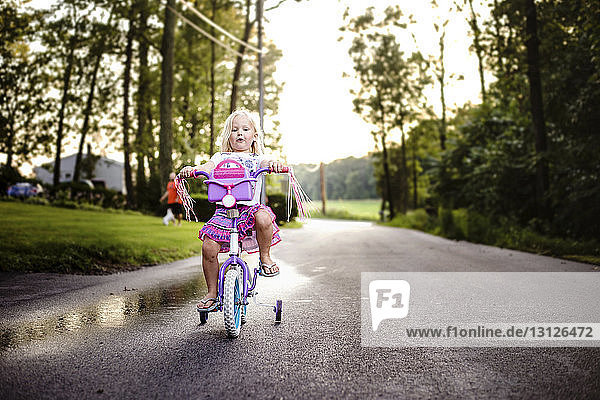 Girl riding bicycle on road at park