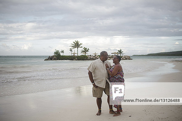 Senior couple standing at beach against cloudy sky