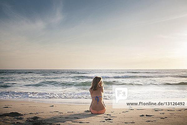 Rückansicht einer Frau  die bei Sonnenuntergang am Strand gegen den Himmel sitzt