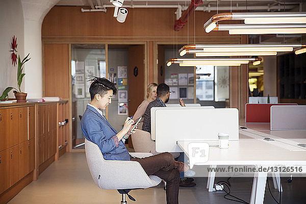 Geschäftsfrau benutzt Mobiltelefon am Tisch mit Kollegen im Hintergrund im Büro