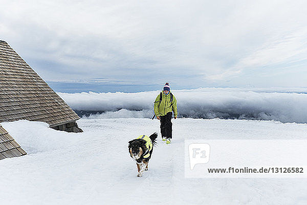 Man walking with dog on snow covered field at Mount Hood against sky