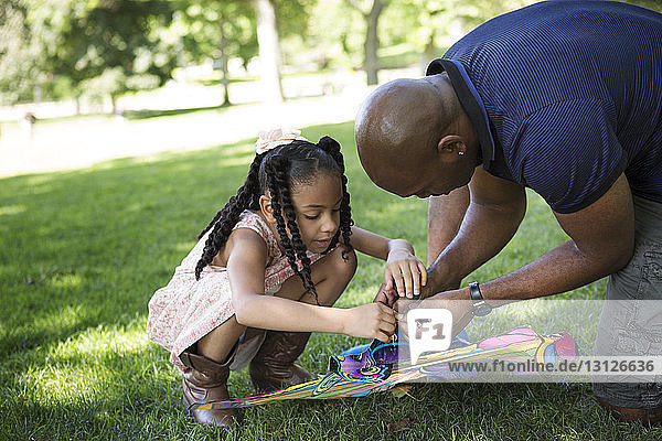 Father and daughter playing checking kite on grassy field