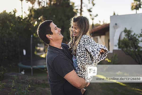 Father carrying daughter while standing in yard