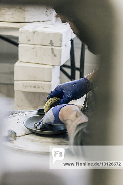 Close-up of craftsman using pottery wheel while working in art studio