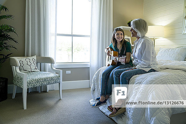 Granddaughter playing guitar while sitting by grandmother on bed