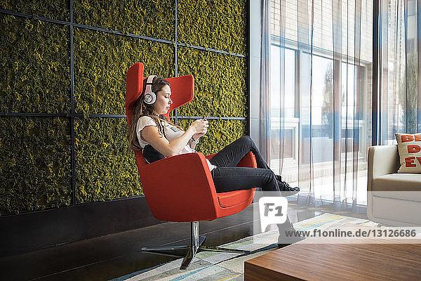 Seitenansicht einer Frau  die zu Hause auf einem Sessel sitzend Musik hört