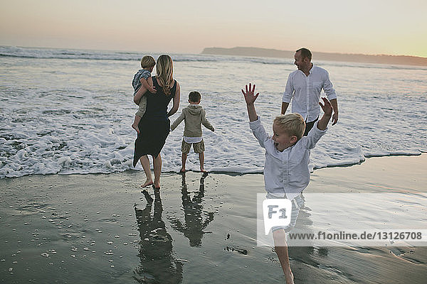 Happy family playing at beach during sunset