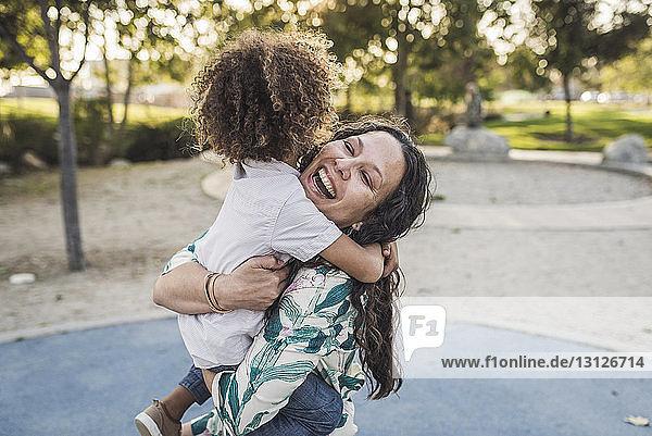 Fröhliche Mutter umarmt Sohn im Park