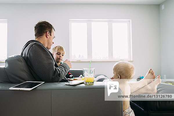 Father feeding breakfast to sons while sitting on sofa at home